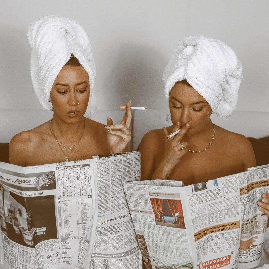 two women reading newspapers while smoking mountain smokes hemp cbd smokes